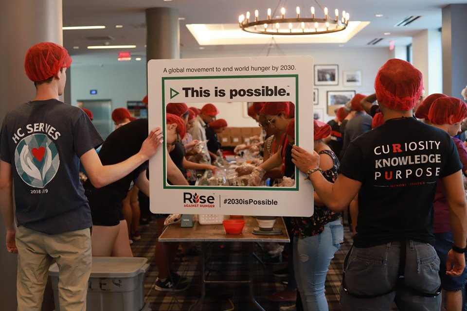 "Students packaging meals and holding a sign that says, ""This is Possible"" referencing ending hunger by 2030"