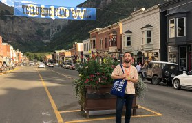 Student standing on street in Telluride with film festival banner behind
